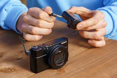A person connecting the ECM-W2BT with a cable to a compatible camera via a 3.5mm stereo mini-jack